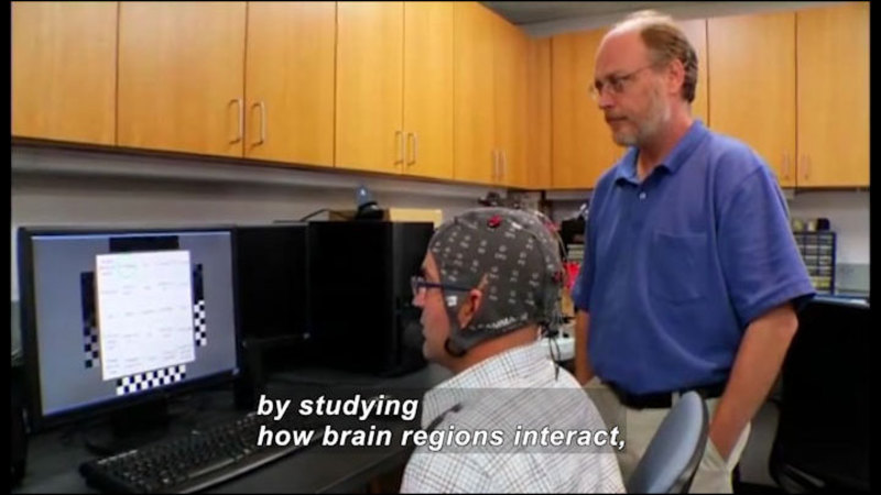 Person wearing a cap with wires and sensors attached while looking at a computer screen. Caption: by studying how brain regions interact,