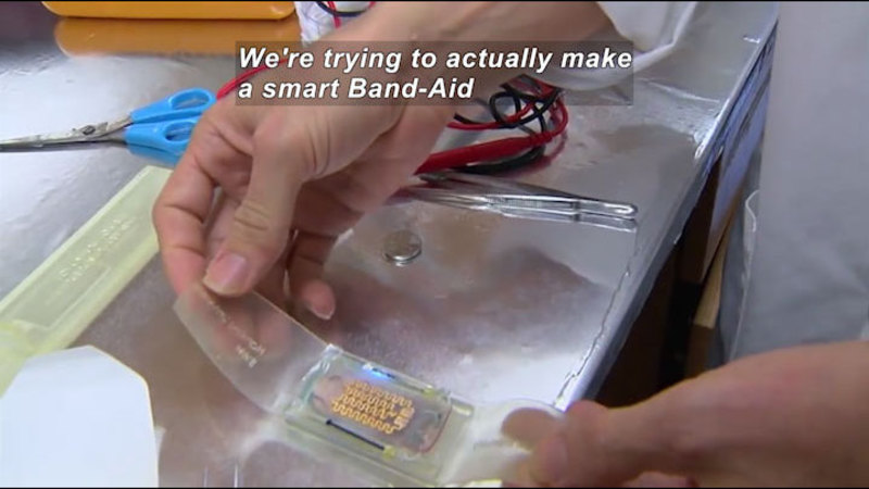 Person in a lab setting with a mostly clear object in their hands. Scissors, wires with leads, and tweezers are on the counter next to them. Caption: We're trying to make a smart Band-Aid