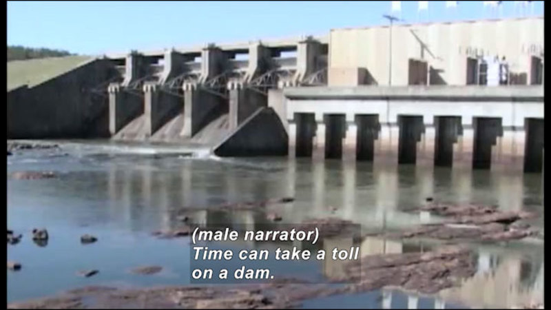 Dam with no water being released. Caption: (male narrator) Time can take a toll on a dam.