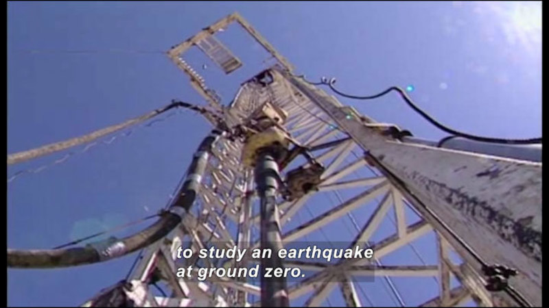 A lattice-work ladder leading to a platform. Instruments and cables are placed on the lattice and platform. Caption: to study an earthquake at ground zero.