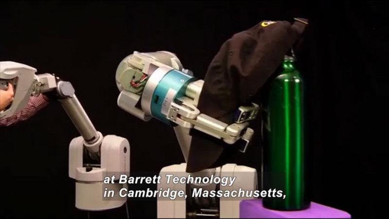 Robotic arm placing a baseball hat on a water bottle. Caption: at Barrett Technology in Cambridge, Massachusetts,