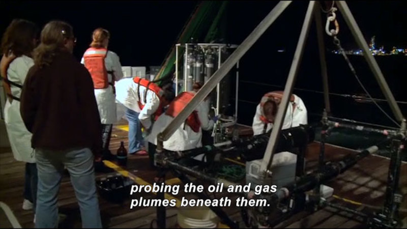 People on the deck of a ship, working on various equipment. Caption: probing the oil and gas plumes beneath them.