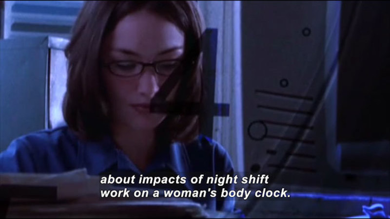 Woman in front of a computer screen in a dimly lit space. Caption: about impacts of night shift work on a woman's body clock.