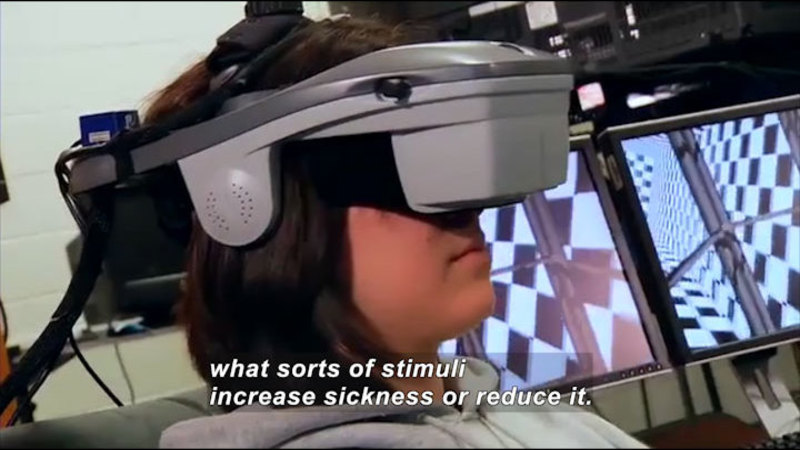 Person with a virtual reality headset on. Caption: what sorts of stimuli increase sickness or reduce it.