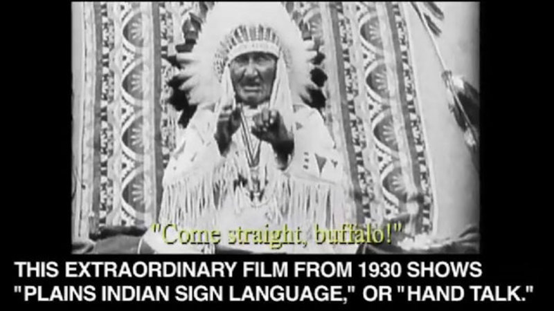 """Native American man in a head dress and traditional clothing gesturing with his hands. Come straight, buffalo! Caption: This extraordinary film from 1930 shows """"Plains indian sign language,"""" or """"Hand talk."""""""