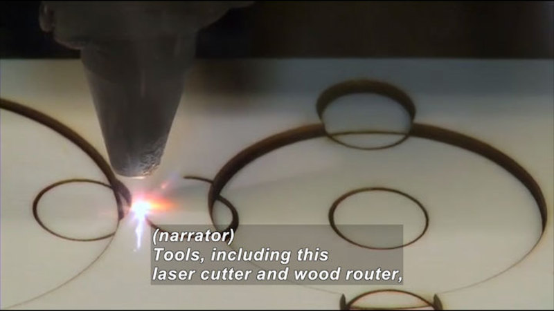 Tool emitting bright light cutting circles into wood. Caption: (narrator) Tools, including this laser cutter and wood router,