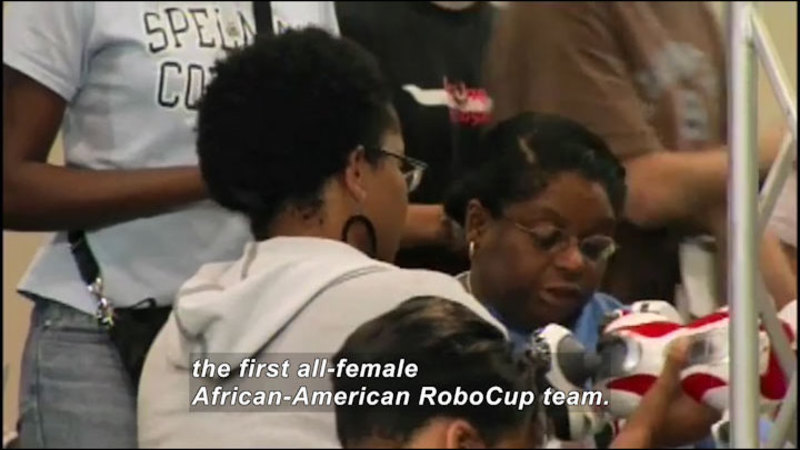 Several young people working on an object. Caption: the first all-female African-American RoboCup team.