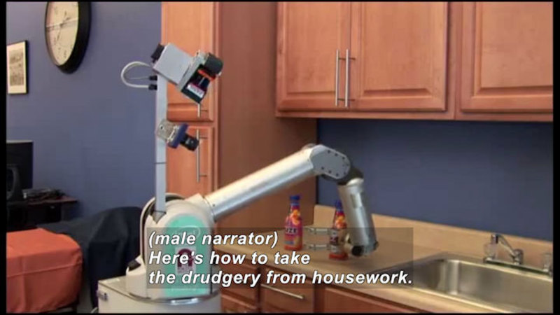 Robot with an arm moving bottles next to a sink. Caption: (male narrator) Here's how to take the drudgery from housework.
