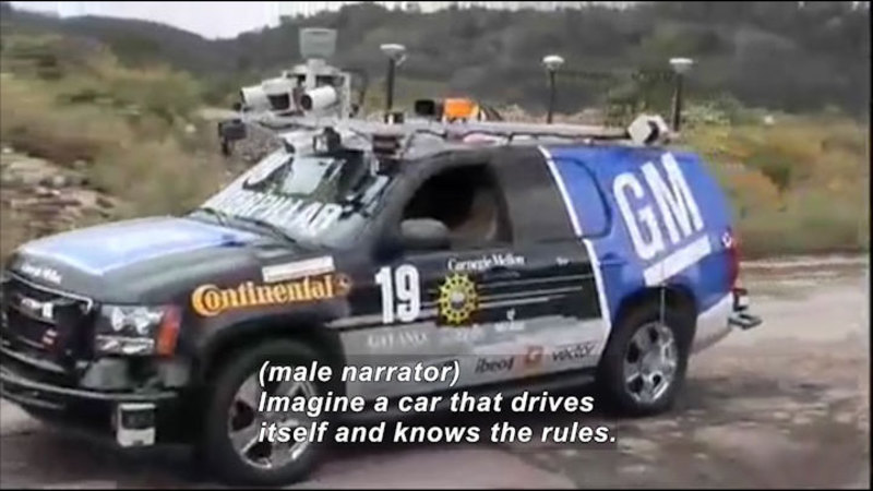 SUV with sensors, cameras, and other equipment attached to the bumper, hood, and roof. Caption: (male narrator) Imagine a car that drives itself and knows the rules.