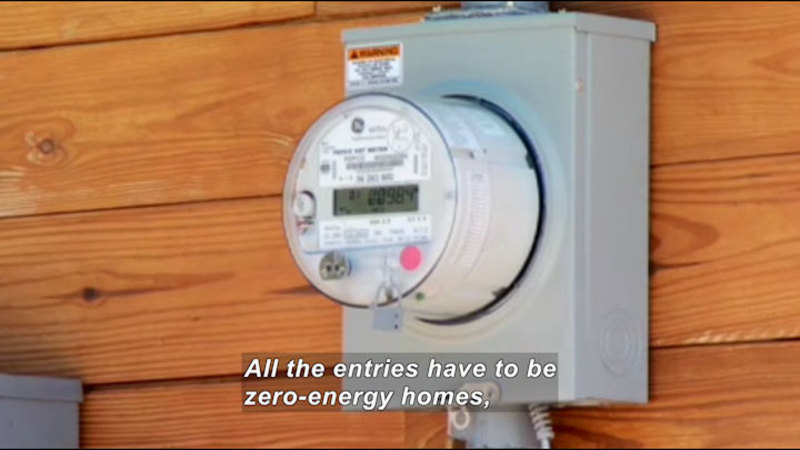 Electrical meter box attached to the outside of a building. Caption: All the entries have to be zero-energy homes,