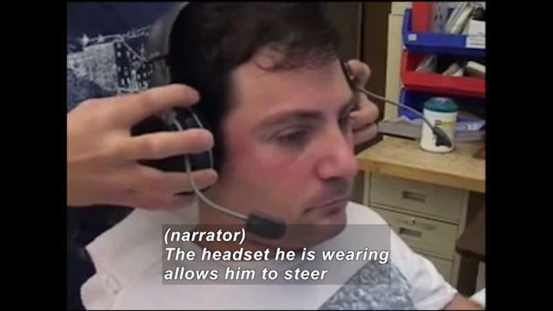 Person with a headset being placed on their head. Caption: (narrator) The headset he is wearing allows him to steer