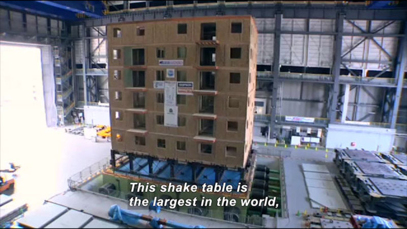 Platform in a warehouse holding a building suspended by struts. Caption: This shake table is the largest in the world,