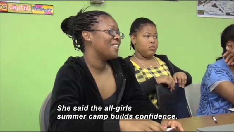 Three young women sitting at a table. Caption: She said the all-girls summer camp builds confidence.