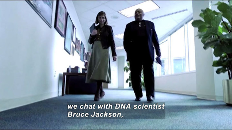 Two people walking down a hallway. Caption: we chat with DNA scientist Bruce Jackson,