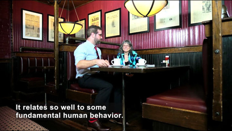 Two people sitting in a booth at a restaurant. Caption: It relates so well some fundamental human behavior.
