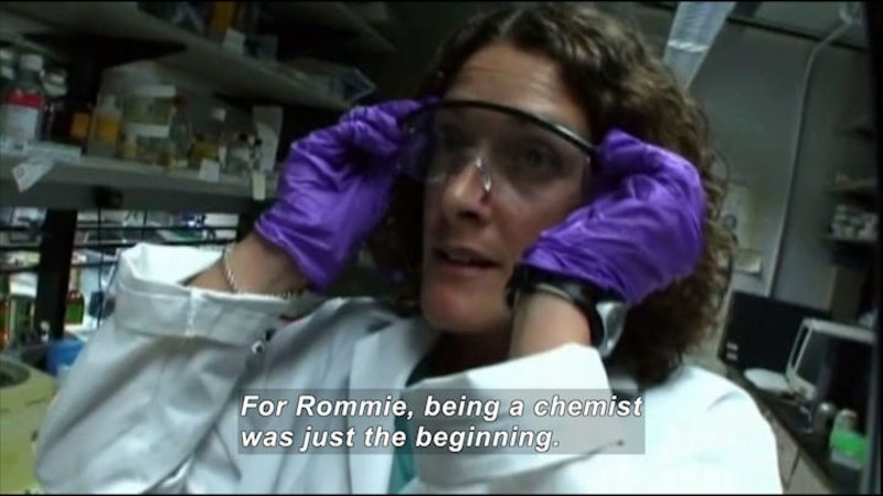 Person in a lab coat and gloves putting on protective glasses. Caption: For Rommie, being a chemist was just the beginning.