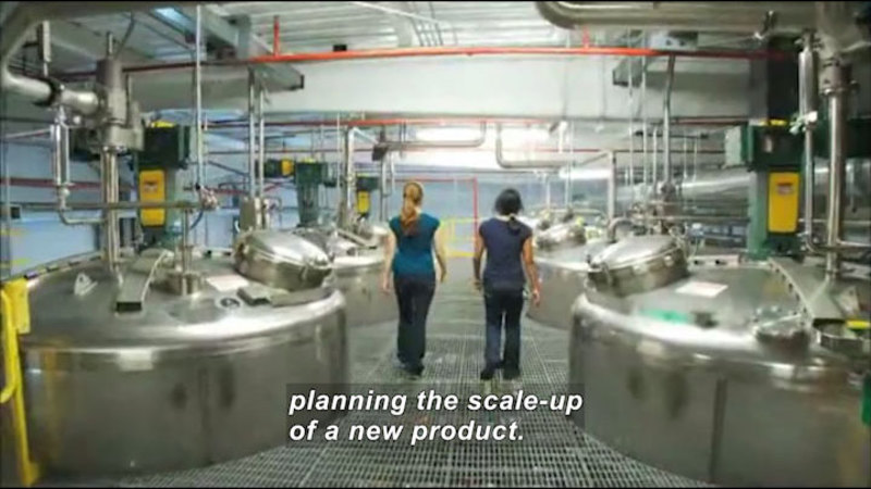 Two people walking next to rows of industrial tanks with piping and gauges. Caption: planning the scale-up of a new product.