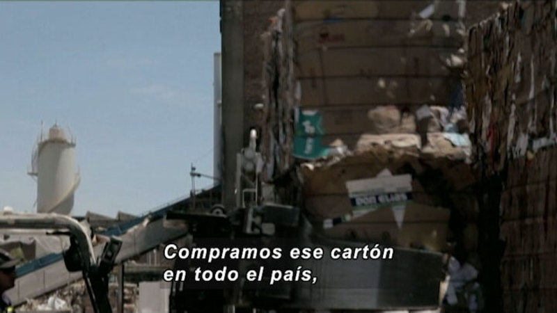 Giant stacks of compressed paper material being moved by industrial machinery. Spanish captions.