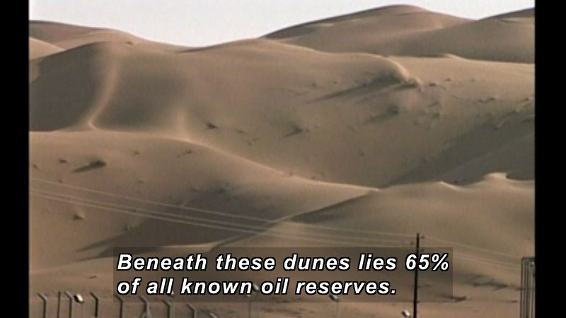 Rolling sand dunes with powerlines in the foreground. Caption: Beneath these dunes lies 65% of all known oil reserves.