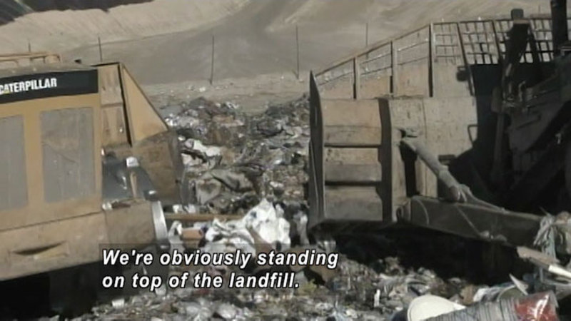 Large machinery on piles of garbage. Caption: We're obviously standing on top of the landfill.