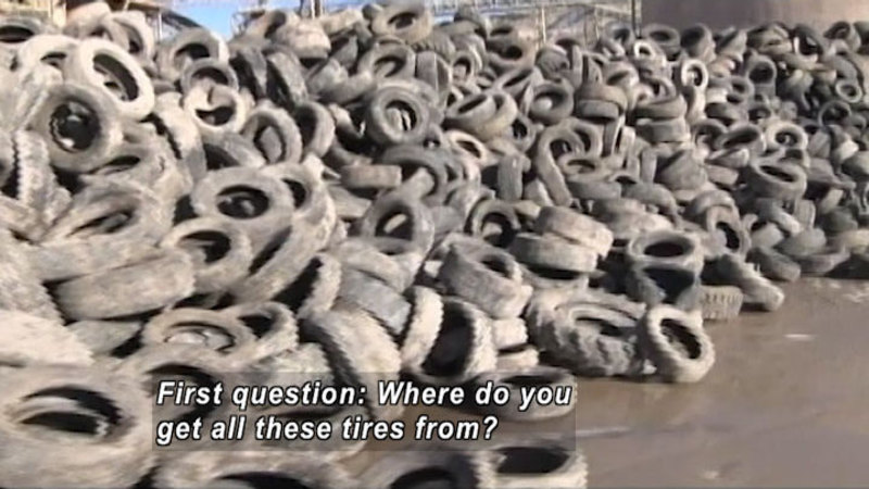 Long pile of thousands of old, dirty tires. Caption: First question: Where do you get all these tires from?