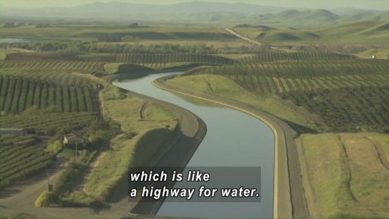 Curving river with unnaturally even banks winds through green fields. Caption: which is like a highway for water.