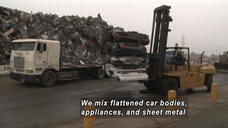 Industrial forklift moving several flattened cars. A giant pile of shredded metal in the background. Caption: We mix flattened car bodies, appliances, and sheet metal