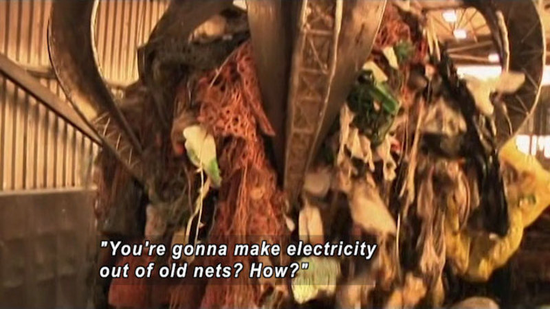 """Industrial metal pinchers pick up a giant pile of discarded fishing nets. Caption: """"You're gonna make electricity out of old nets? How?"""""""