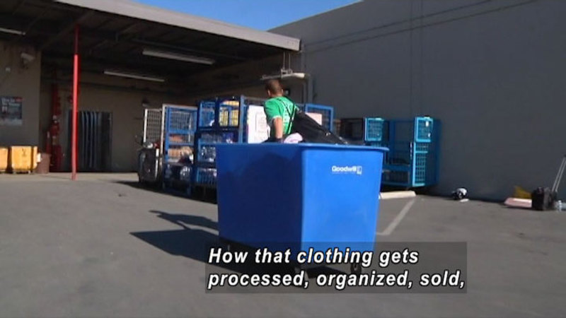"""Person pulling a blue bin with """"Goodwill"""" printed on it across a paved loading dock. Caption: How that clothing gets processed, organized, sold,"""