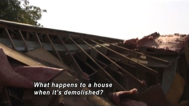 The exposed spine of a roof with insulation and plywood falling around it. Caption: What happens to a house when it's demolished?