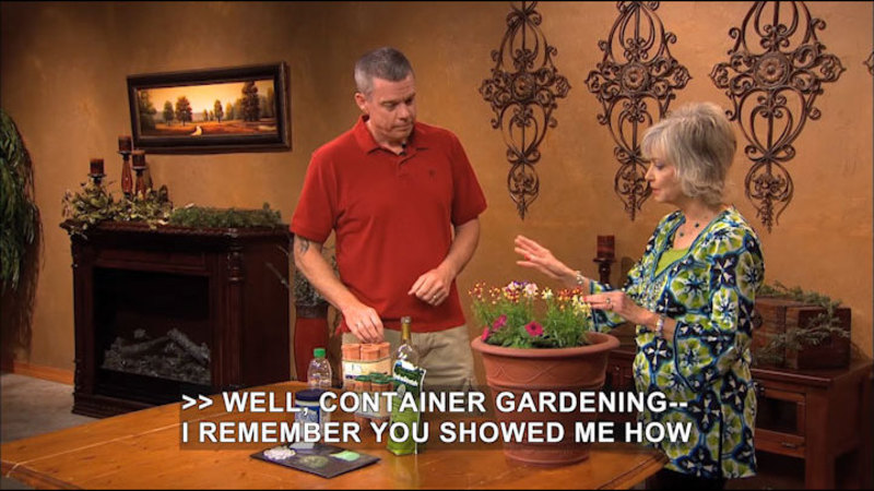 Two people with a large planter in front of them on the table. The planter has flowers growing in it and there are items on the table. Caption: Well, container gardening -- I remember you showed me how