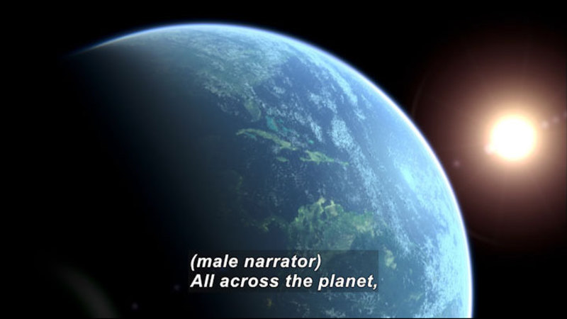 Earth as seen from space with the Sun visible behind it. Caption: (male narrator) All across the planet,