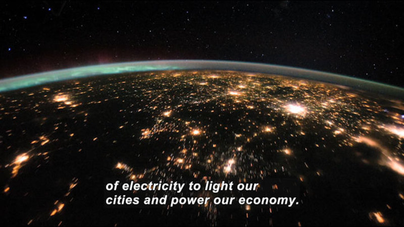Earth at night as viewed from space. A network of glowing light is visible in unpopulated areas across the globe. Caption: of electricity to light our cities and power our economy.