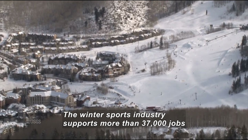 Multiple multistory snow covered building complexes at the foot of snow-covered slopes. Caption: The winter sports industry supports more than 37,000 jobs
