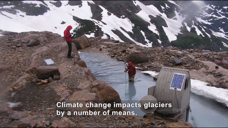 Two people at a glacier. Snow on the mountain in the background, one person standing on a rocky riverbank, the second person in the river with a measurement tool. Caption: Climate change impacts glaciers by a number of means.