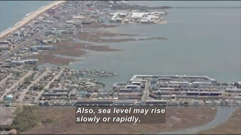 Ocean shoreline on one side and rising water on the other encircle a strip of densely populated buildings. Caption: Also, sea level may rise slowly or rapidly,