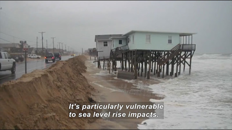 Rough ocean lapping against dirt and sand embankment against a road with vehicles driving on it. Two houses over the water on stilts are starting to fall into the ocean. Caption: It's particularly vulnerable to sea level rise impacts.