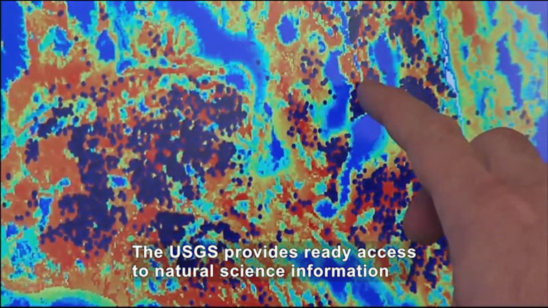 Person pointing to a spot on an image made of pixelated yellow to indigo spots. Caption: The USGS provides ready access to natural science information