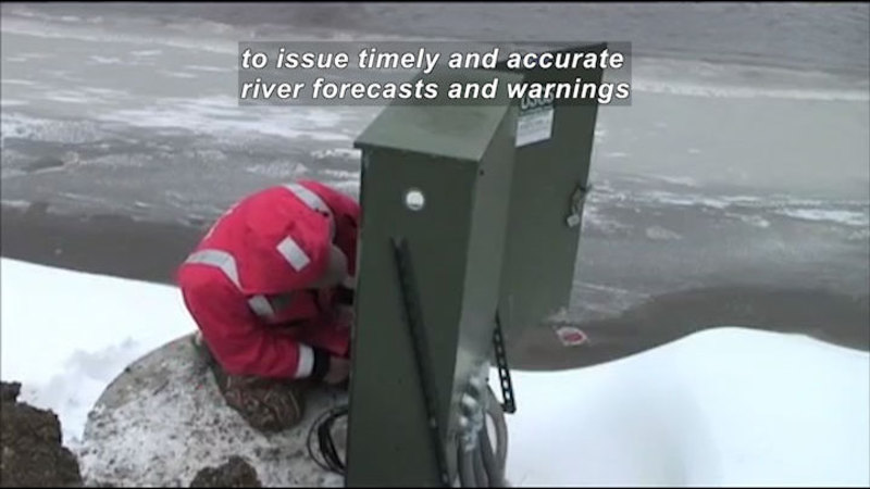 Person crouched next to an electrical box on the bank of a river. Caption: to issue timely and accurate river forecasts and warnings