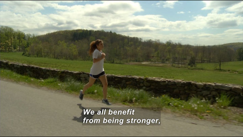 Person in shorts and a t-shirt running by a green field. Caption: We all benefit from being stronger,