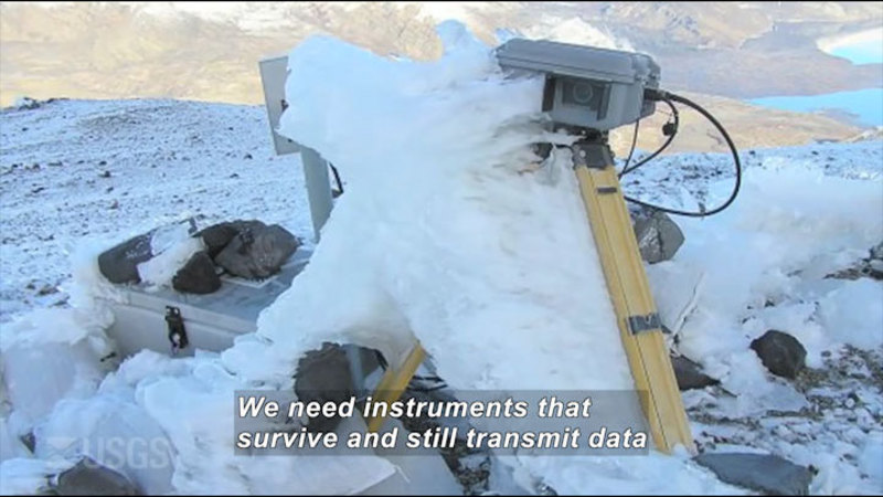 Camera on a tripod next to other equipment, covered in ice and snow. Caption: We need instruments that survive and still transmit data