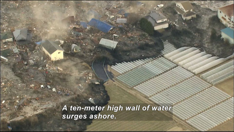 Debris filled water carries buildings and cars over cultivated fields. Caption: A ten-meter high wall of water surges ashore.