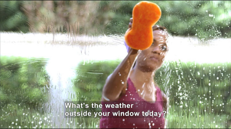A person washing a window with a sponge. Caption: What's the weather outside your window today?