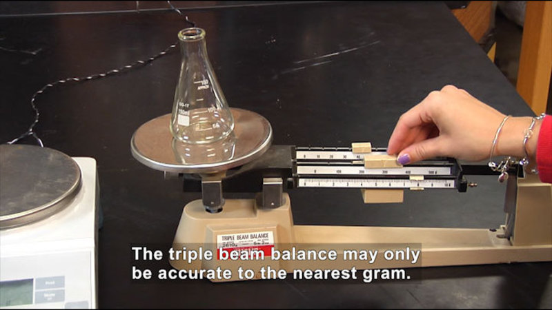 Person weighing a beaker on a triple beam scale. Caption: The triple beam balance may only be accurate to the nearest gram.