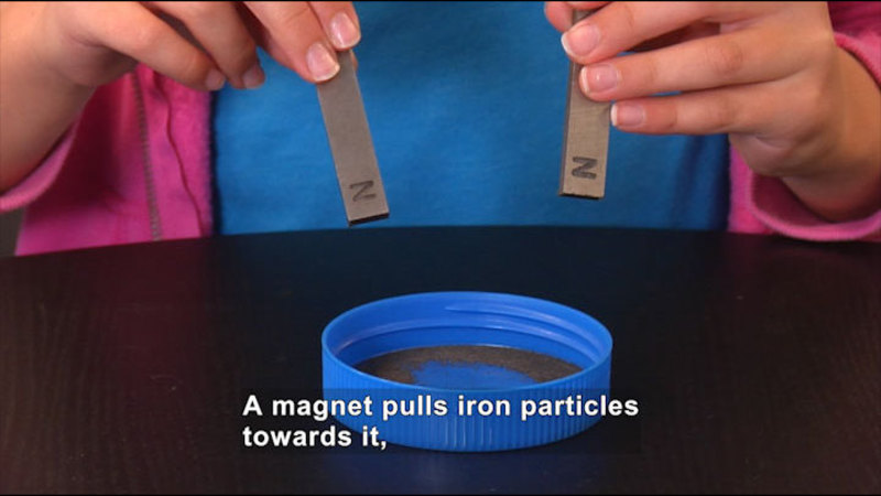 A person holds two magnets over a lid with metal particles in the bottom. Caption: A magnet pulls iron particles towards it,