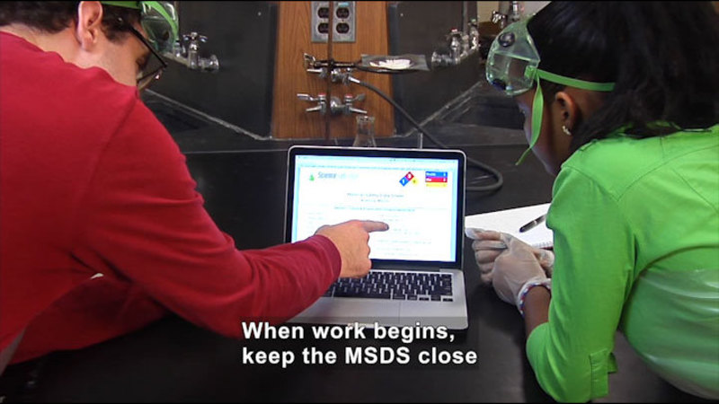 Two people looking at a laptop screen. Caption: When work begins, keep the MSDS close