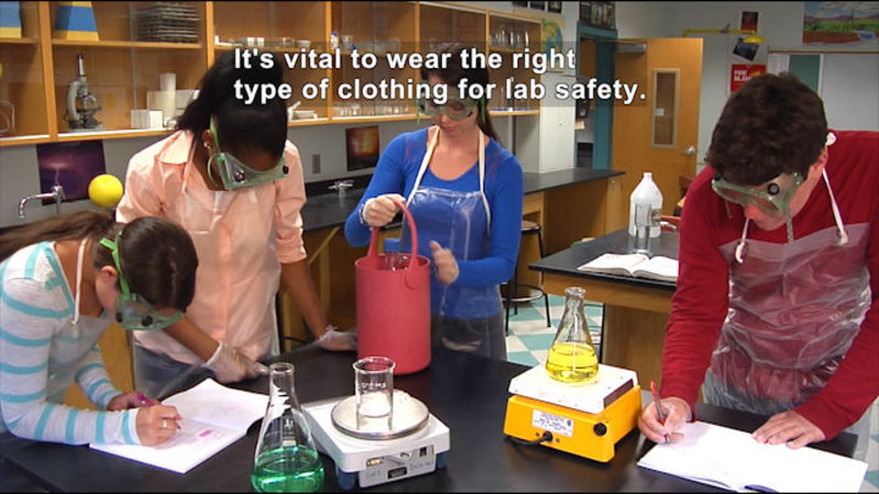 People wearing rubber gloves, plastic aprons, and protective goggles in a science classroom. Caption: It's vital to wear the right type of clothing for lab safety.