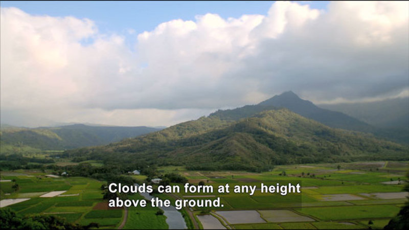 Green patchwork fields with a mountain rising in the background. Clouds cover most of the blue sky. Caption: Clouds can form at any height above the ground.