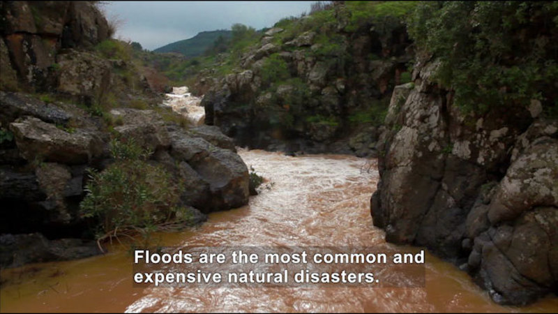 Muddy water rushing through a rocky channel. Caption: Floods are the most common and expensive natural disasters.
