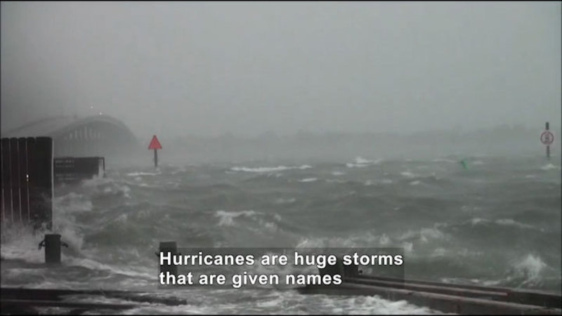 Rough ocean water covering beach and surrounding areas. Caption: Hurricanes are huge storms that are given names